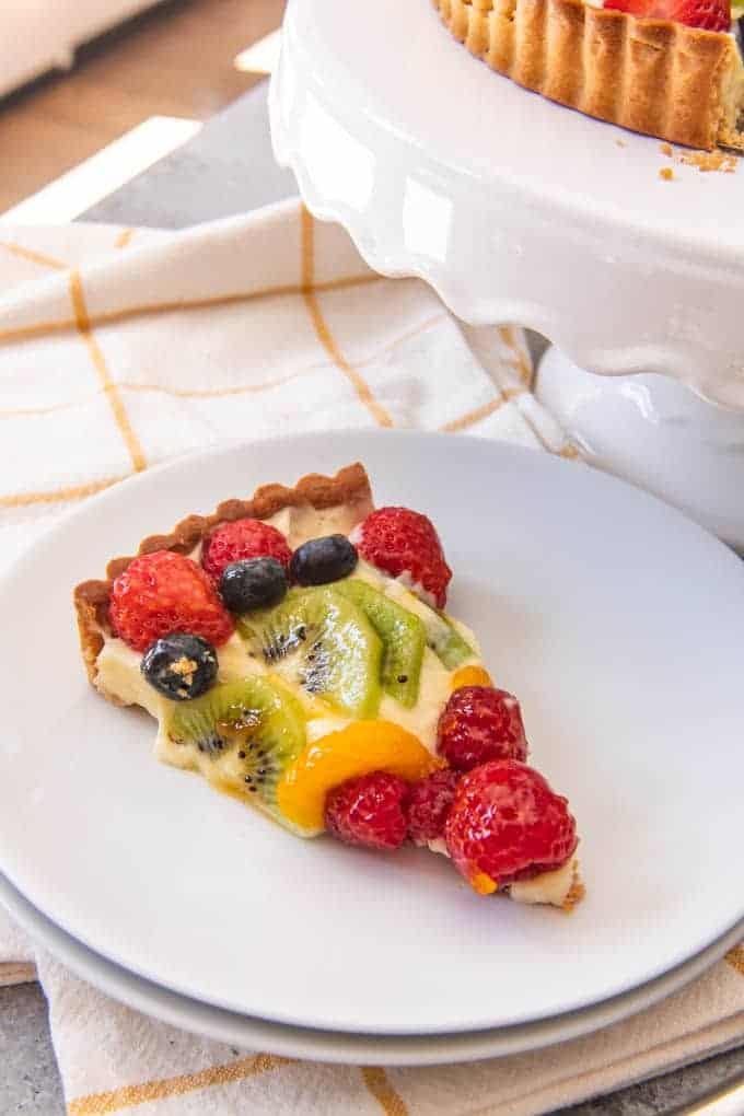 An image of a slice of mixed fruit tart made with pastry cream and a pate sucree sweet pastry crust.