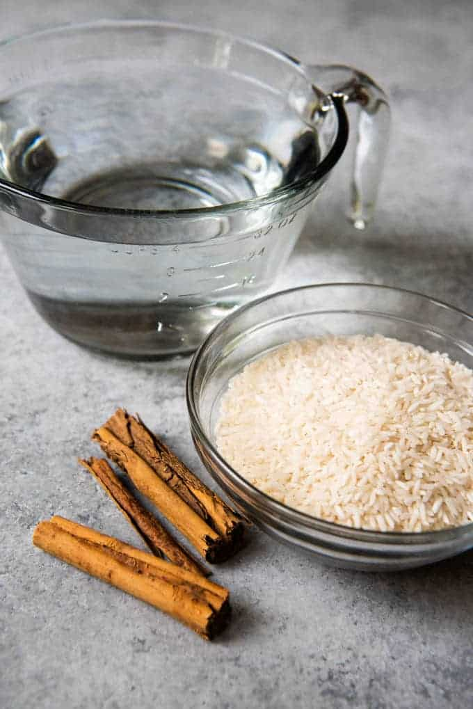 An image of a bowl of uncooked rice, Mexican cinnamon sticks, and water, ready to be combined to make authentic horchata.