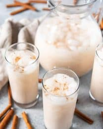 A pitcher of ice cold horchata next to cups of horchata and sticks of cinnamon