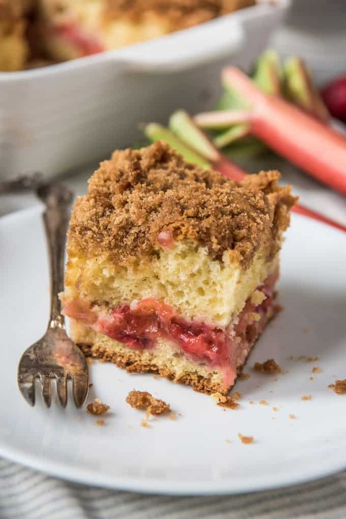 An image of a slice of cinnamon crumb coffee cake with a thick layer of strawberry rhubarb filling in the middle.