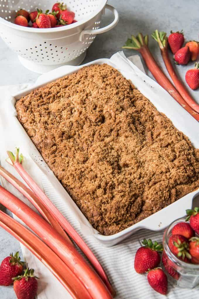 A large pan of strawberry rhubarb coffee cake, surrounded by rhubarb stalks and strawberries.