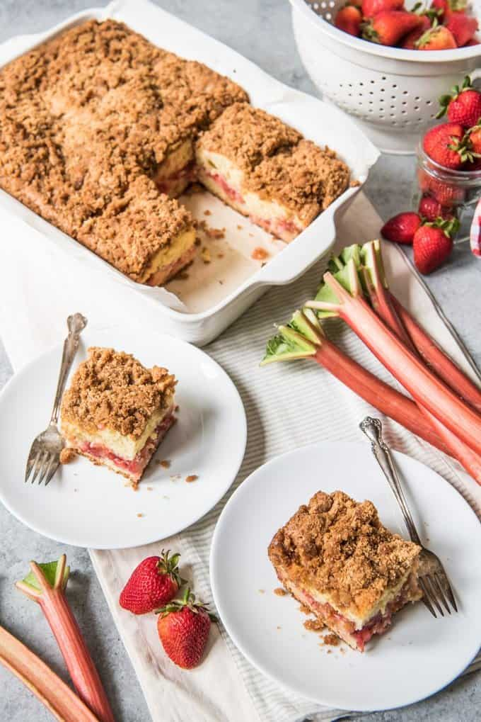 There is nothing like starting your morning (or ending your day!) with a big slice of delicious, strawberry rhubarb coffee cake.  With a layer of bright, sweet tart fruit filling baked into a rich, moist cake made with sour cream and finished off with a thick, heavenly layer of buttery brown sugar cinnamon crumb on top, this easy cake is just as happy on the brunch menu as it is on the dessert table.