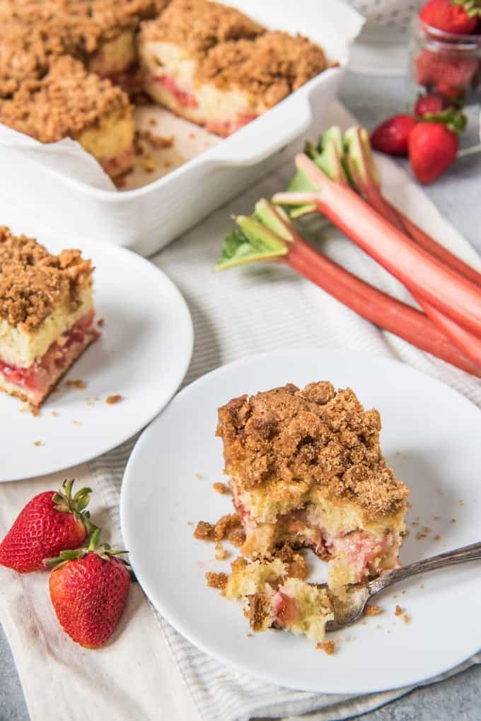 An image of a slice of strawberry rhubarb coffee cake with a large baking dish of coffee cake behind it.
