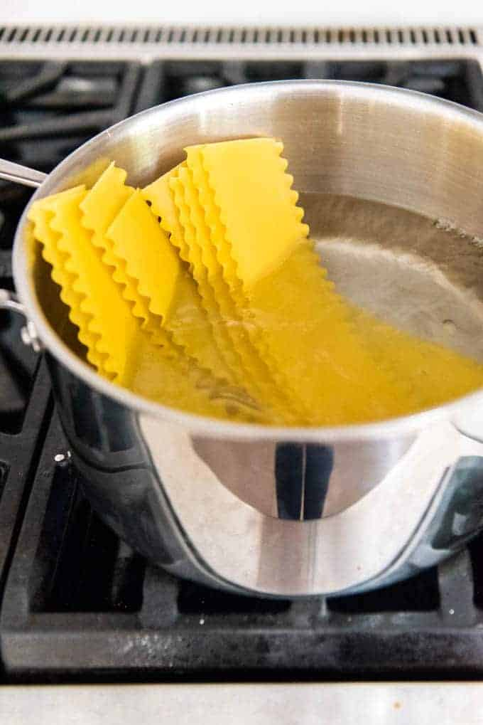 An image of a pot of boiling water with lasagna noodles in it.