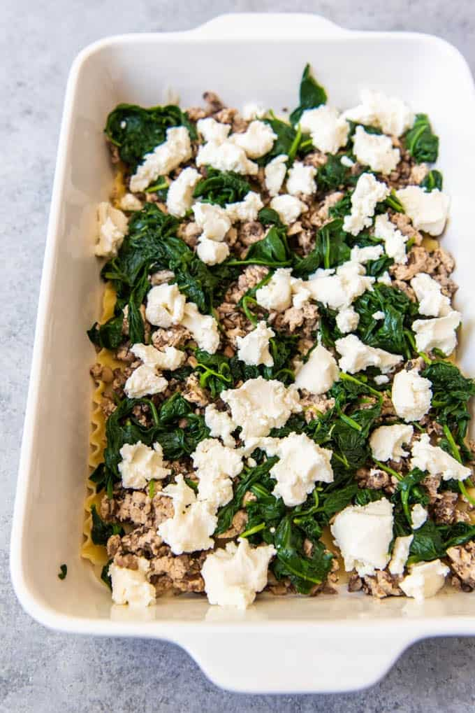 An image of a white chicken spinach lasagna in the process of being assembled with layers of noodles, spinach, ricotta cheese, and browned chicken and mushrooms.
