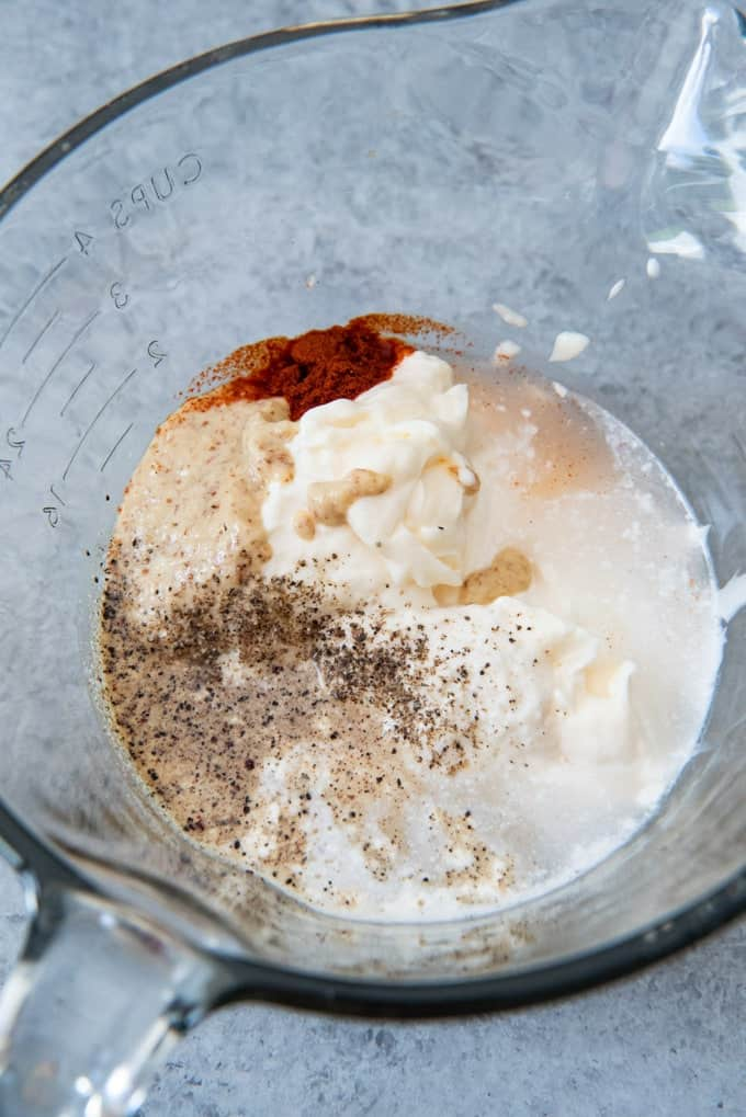 An image of a bowl with mayonnaise, mustard, horseradish, vinegar, pepper, paprika, and garlic powder for making Alabama White Barbecue Sauce.
