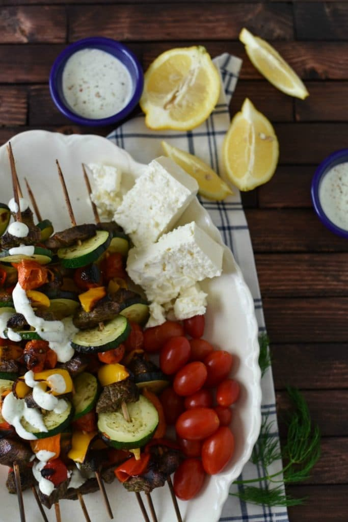 An image of beef souvlaki skewers on a large platter with grape tomatoes and with feta and dill dip on the side.