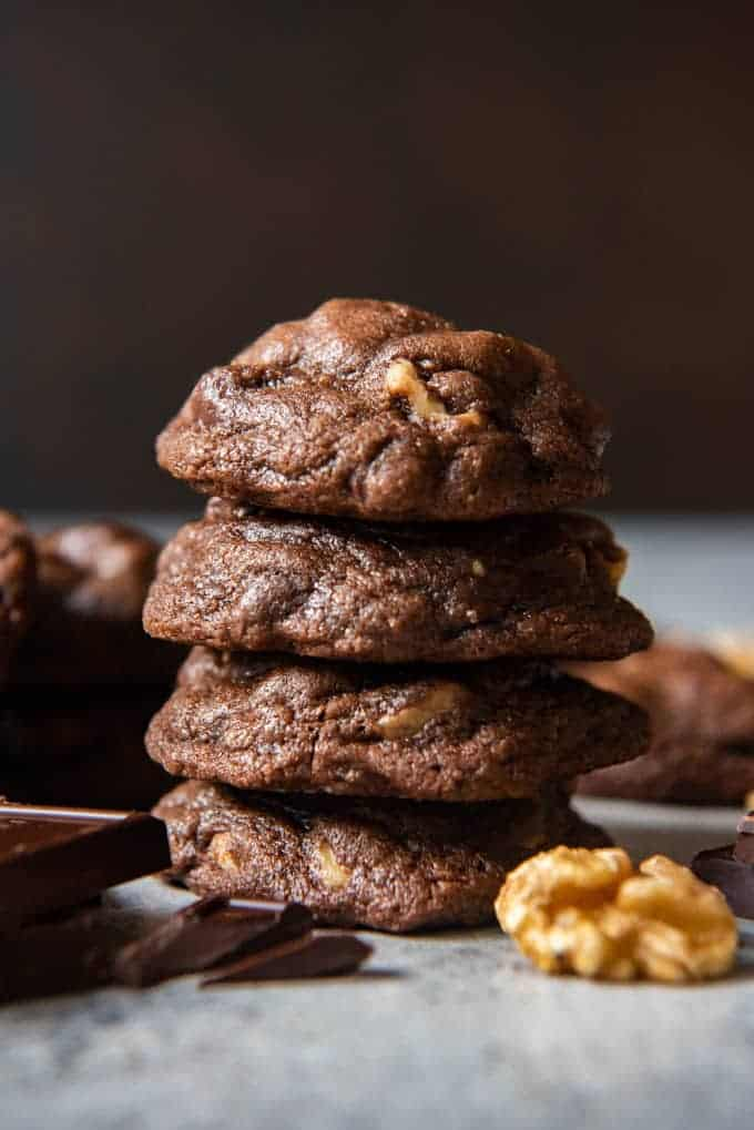 chocolate cookies next to chocolate and a walnut