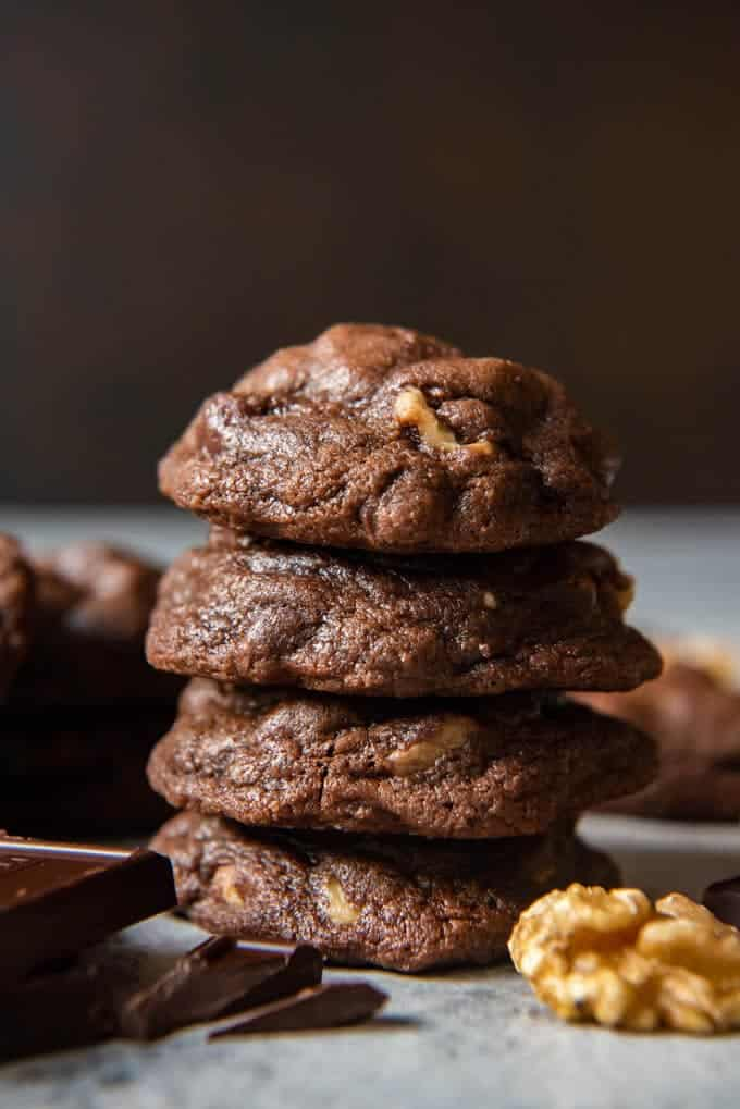 An image of a stack of chocolate brownie cookies with walnuts and chocolate chips.