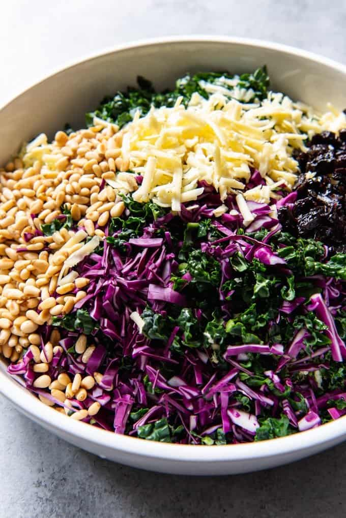 An image of a large white serving bowl with chopped kale, red cabbage, white cheddar cheese, pine nuts, and dried cherries for a chopped kale salad.