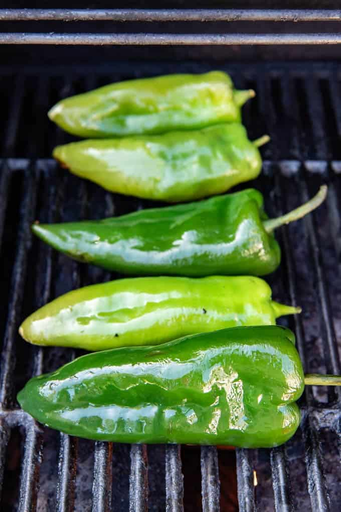 Whole poblano peppers on a grill to be roasted over a flame.