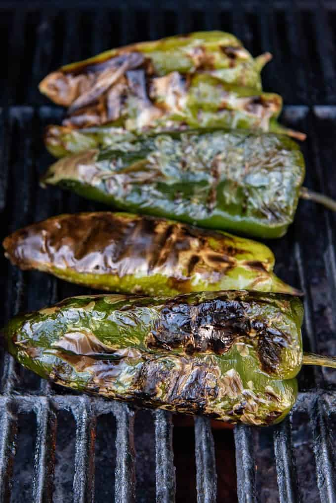 Grilled poblano peppers that have been roasted on a grill over a flame until the skins are charred.