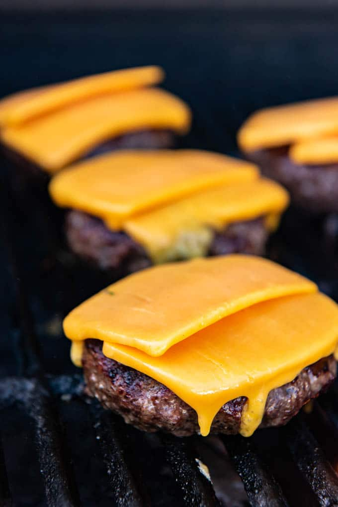 A image of grilled hamburger patties with slices of sharp cheddar cheese melting on top for cheeseburgers.