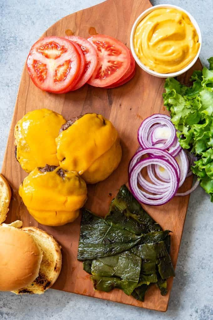 An image of a cutting board with all the things needed for Grilled Poblano Pepper Southwest Burgers like chipotle aioli, cheddar cheese covered hamburger patties, toasted buns, grilled peppers, lettuce, tomatoes, and red onions.