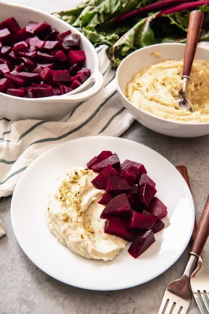 An image of a plate of pantzaria me skordalia, a tradition Greek dish made with roasted beets and a garlic-potato spread, sprinkled with pistachios.