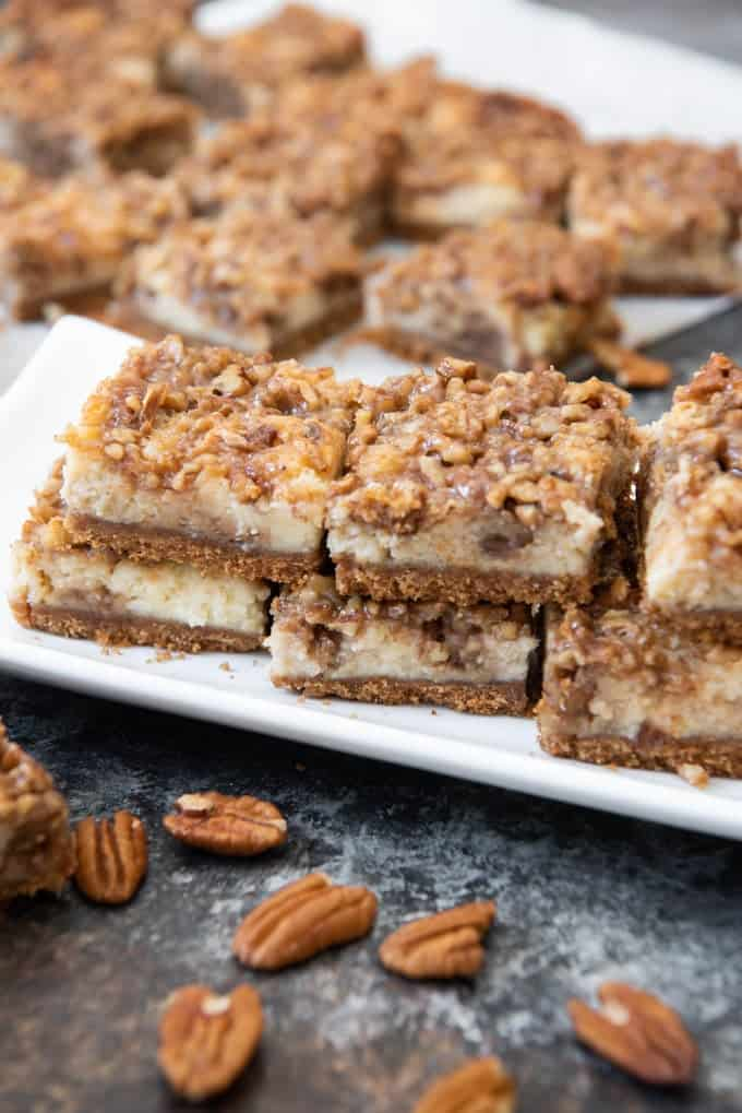 a white plate filled with stacked pecan pie cheesecake bars with scattered whole pecans below