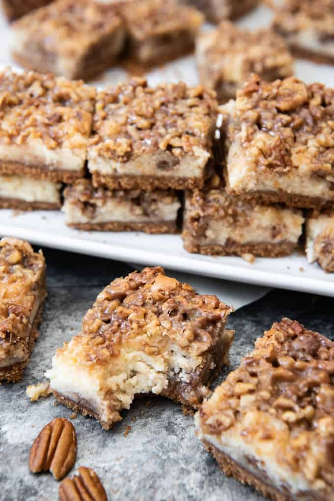 stacked pecan pie bars on a plate with some below one is missing a bite