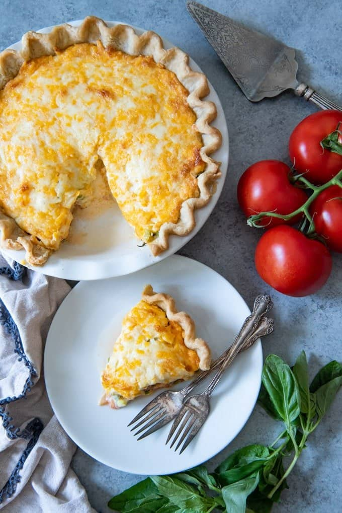 An image of a cheese and tomato pie with one slice removed and set on a white plate next to summer-ripe tomatoes and fresh basil.