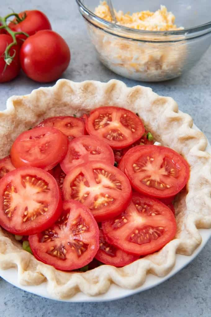 An image of a par-baked pie crust with layers of tomatoes, green onions, and basil, for a southern tomato pie.