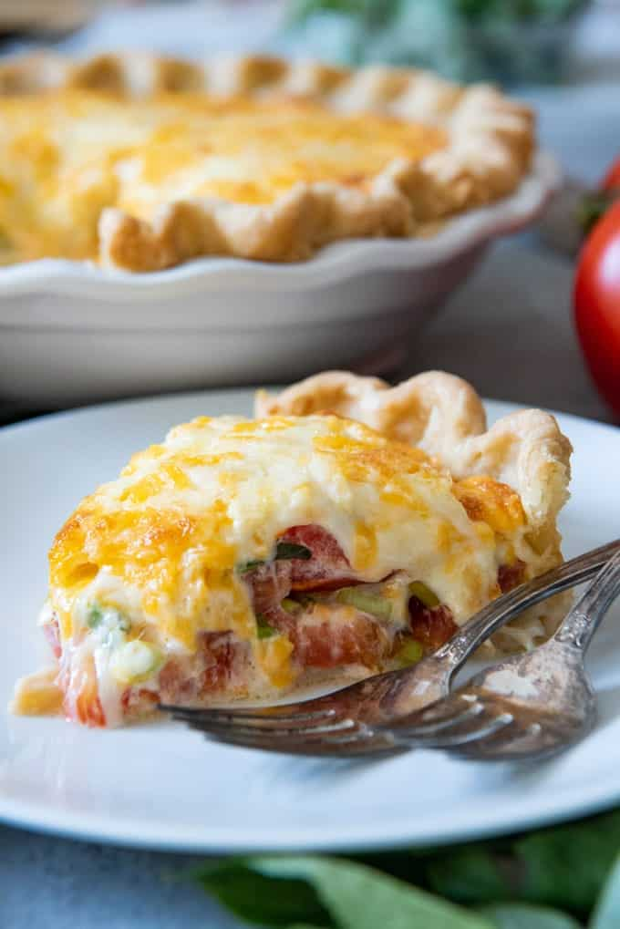 This savory Southern Tomato Pie is made with summer-ripe tomatoes, fresh basil leaves, and topped with a tasty cheese & mayo topping!