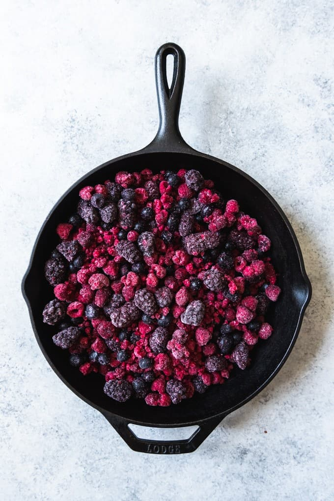 An image of a large cast iron skillet with frozen mixed berries in it to be used as the filling for a mixed berry cobbler.