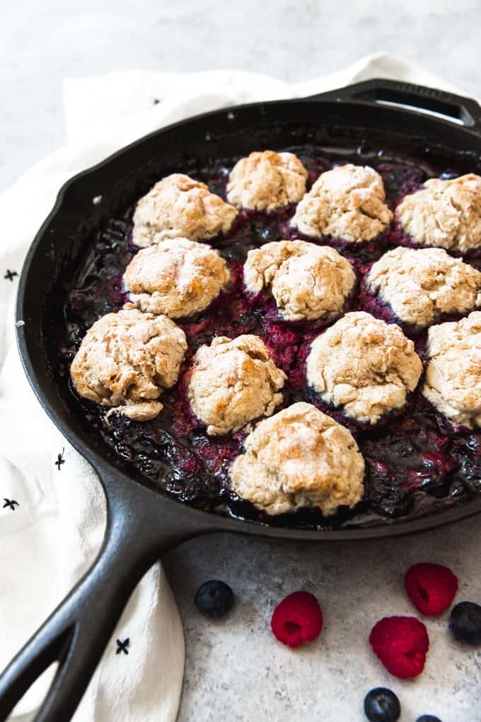 a cast iron skillet with berr cobbler and biscuits