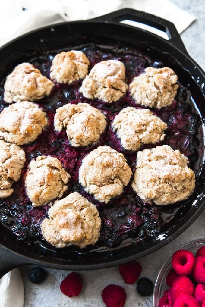 An image of a mixed berry cobbler recipe using frozen fruit with a buttermilk biscuit topping.