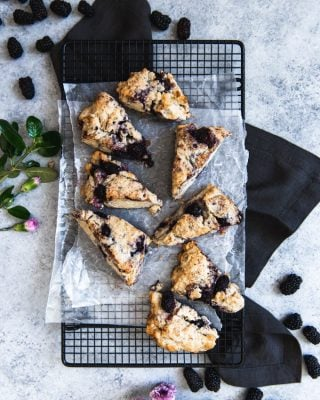 an aerial view of blackberry scones on wax paper on a wire rack with fresh flowers and berries to the side