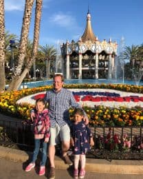 a man and two daughters standing near a tourist attraction