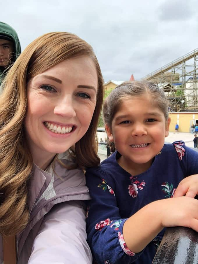 An image of a mom and daughter smiling at an amusement park.
