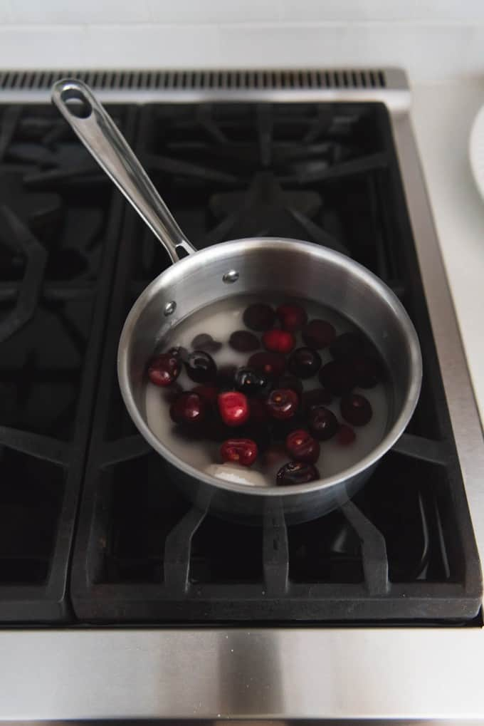 An image of a saucepan with cherries, sugar, and water for poaching and putting into cherry vanilla ice cream.