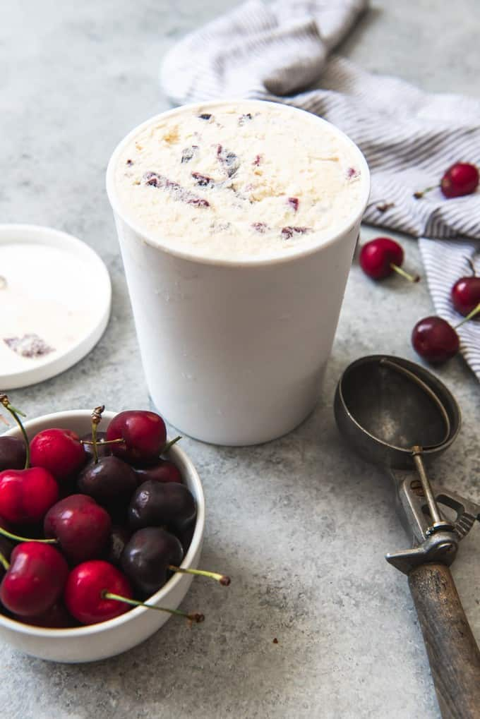 An image of a container of homemade cherry vanilla ice cream with a bowl of cherries and an ice cream scoop nearby.