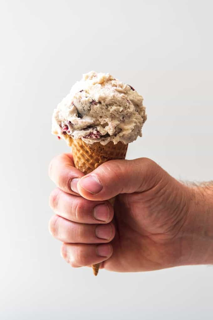 An image of a hand holding a sugar cone with a scoop of cherry vanilla ice cream.