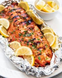 a grilled salmon in a foil packet with lemon wedges