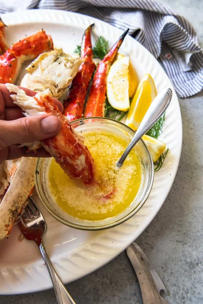 An image of a hand dunking a large chunk of Alaskan King Crab Leg meat into melted garlic butter.