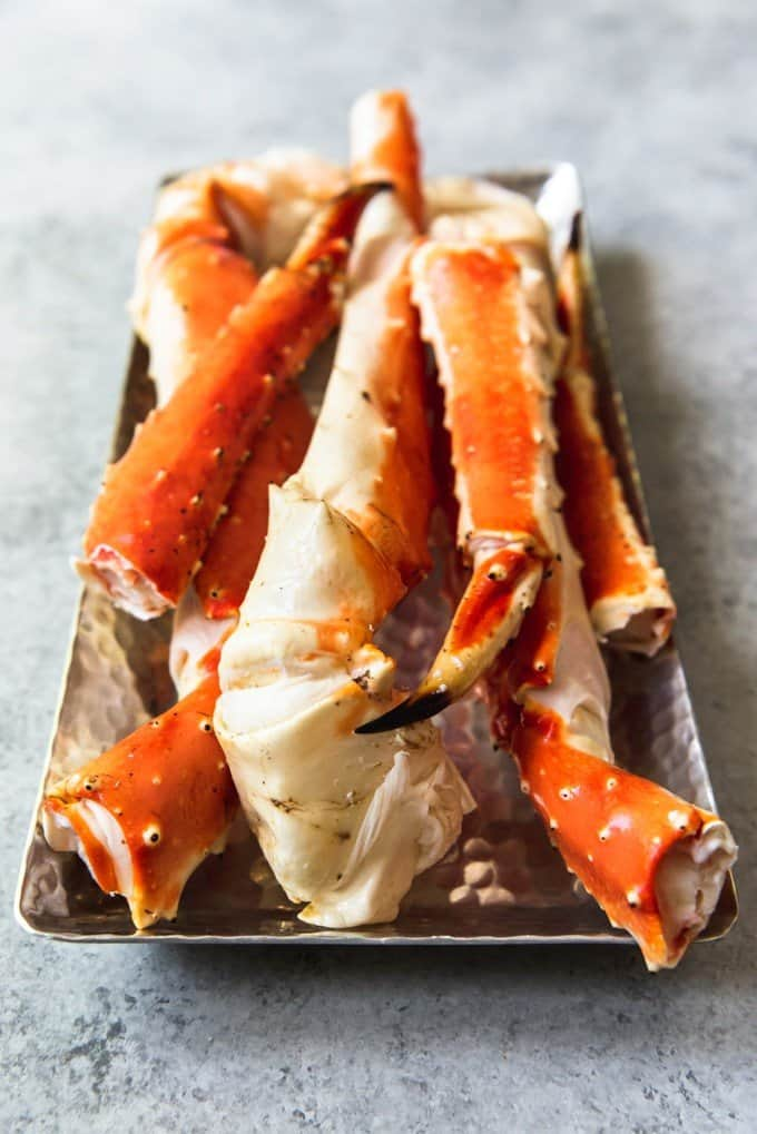An image of a platter of Alaskan King Crab Legs, ready to go onto the grill, is an easy solution for how to cook frozen crab legs.