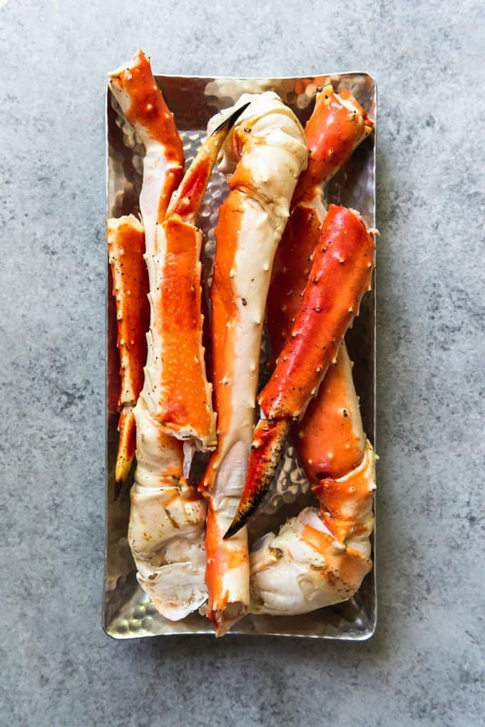 An image of a plate full of defrosted Alaskan King Crab Legs, ready to go on the grill.