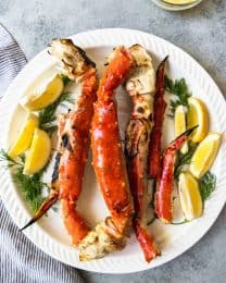 an aerial view of a plate filled with cooked crab legs and garnished with lemon slices and fresh herbs