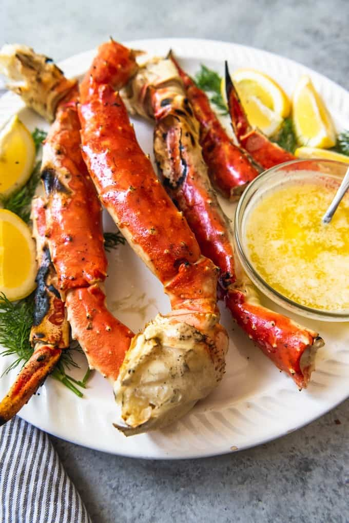 An image of a large platter of Alaskan king crab legs garnished with fresh dill, lemon wedges, and garlic butter.