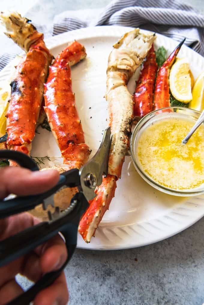 An image of a platter of Alaskan King Crab Legs being cut open with kitchen shears to get to the crab meat inside.