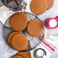Joe Froggers Cookies scattered around a wire rack with measuring cups and tools to the side