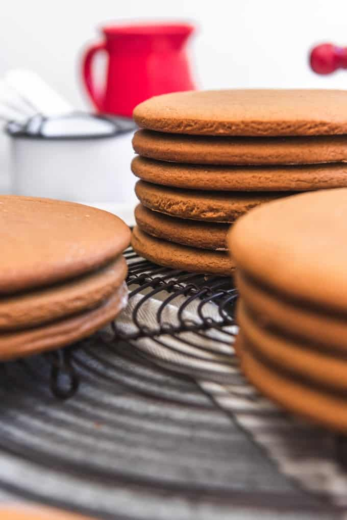 Stacks of large molasses cookies called Joe Froggers on a wire cooling rack.