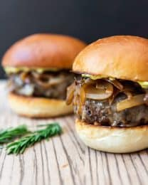 two soy glazed mushroom swiss burgers with carmelzides onions and two sprgs of fresh rosemary to the side