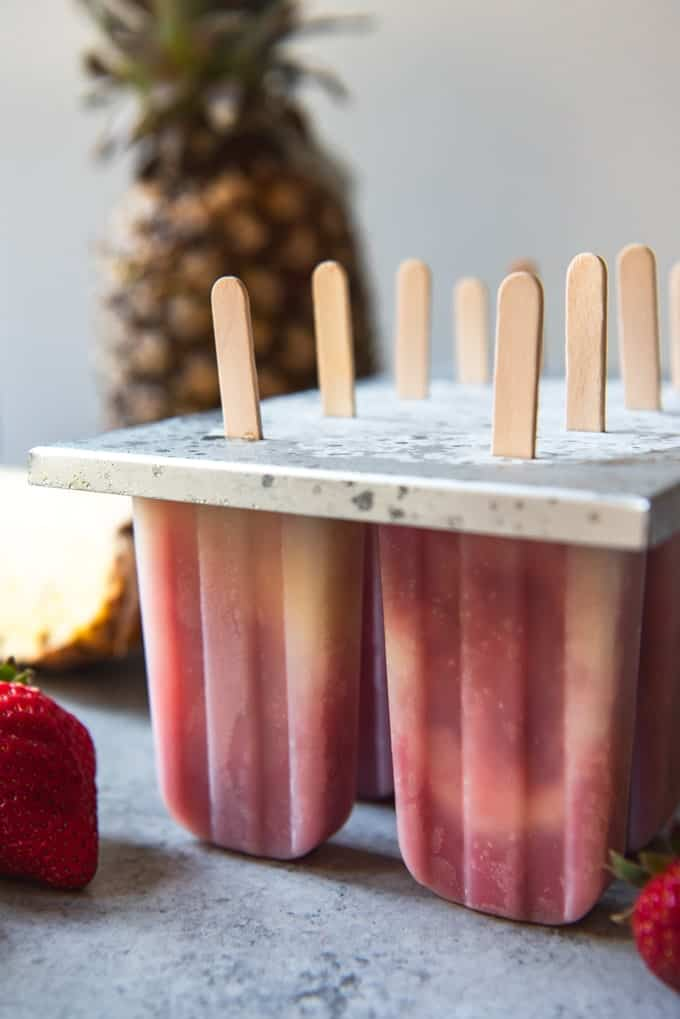 An image of pineapple strawberry coconut popsicles in a popsicle mold right out of the freezer.