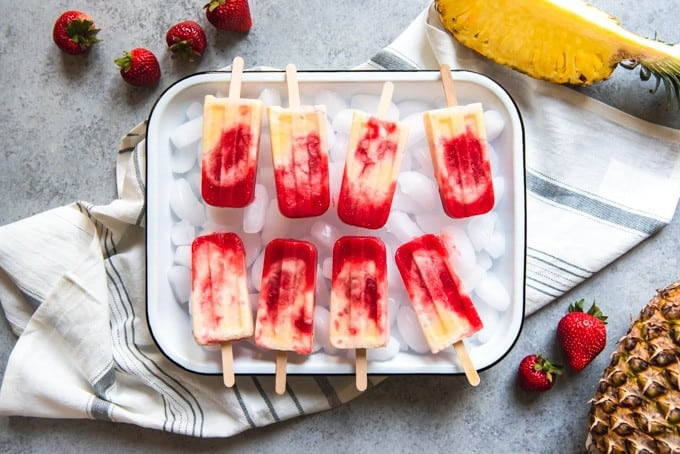 An image of a tray of strawberry pineapple coconut swirl popsicles arranged on a bed of ice cubes, surrounded by fresh strawberries and pineapple.