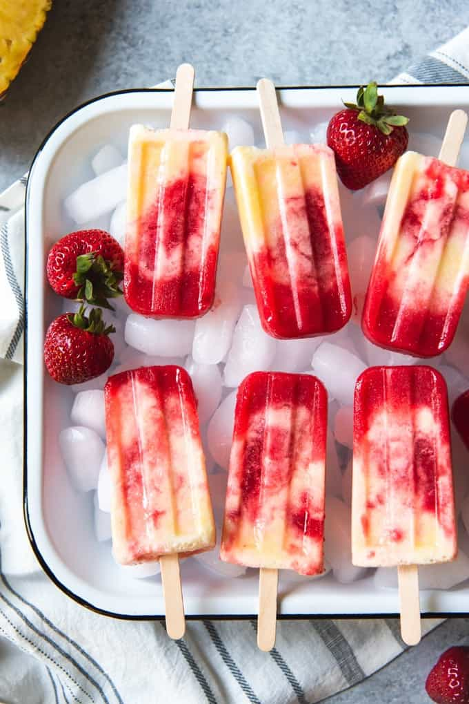 a baking dish full of ice topped wth fresh strawberries and strawberry pineapple coconut swirl popsicles