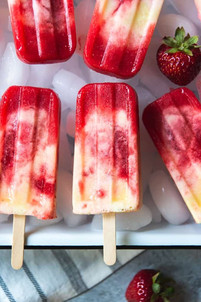 An image of swirled strawberry pineapple popsicles with a hint of coconut.