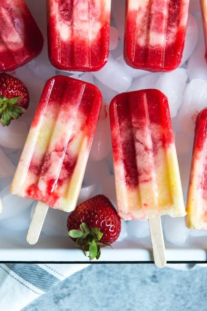 An image of two strawberry pineapple coconut swirl popsicles side by side on a bed of ice cubes.