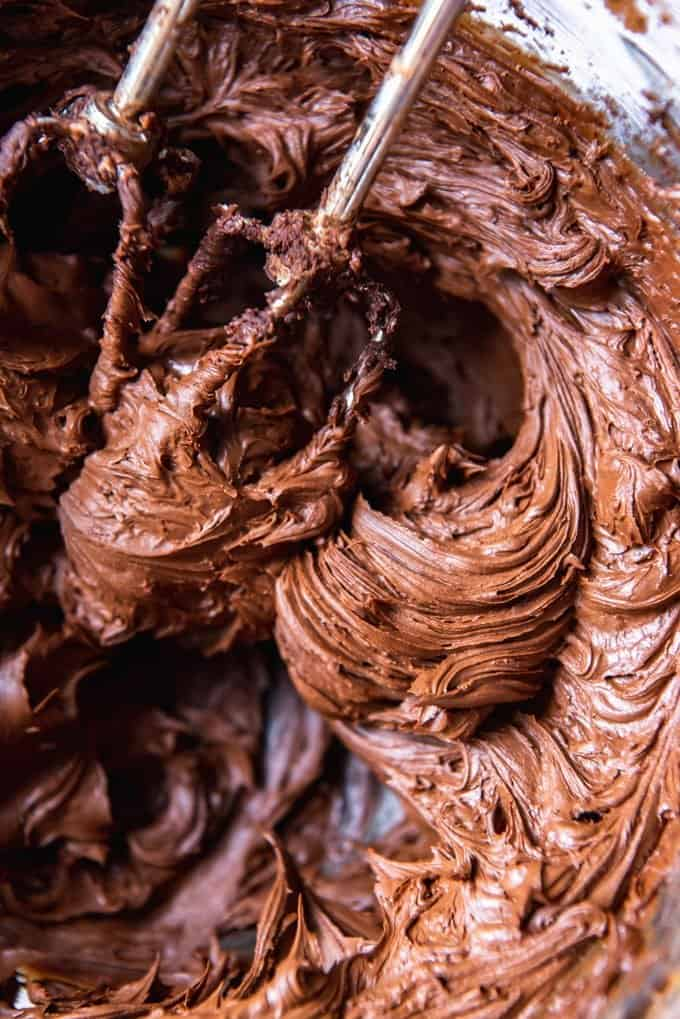 An image of homemade chocolate frosting in a bowl with beaters.