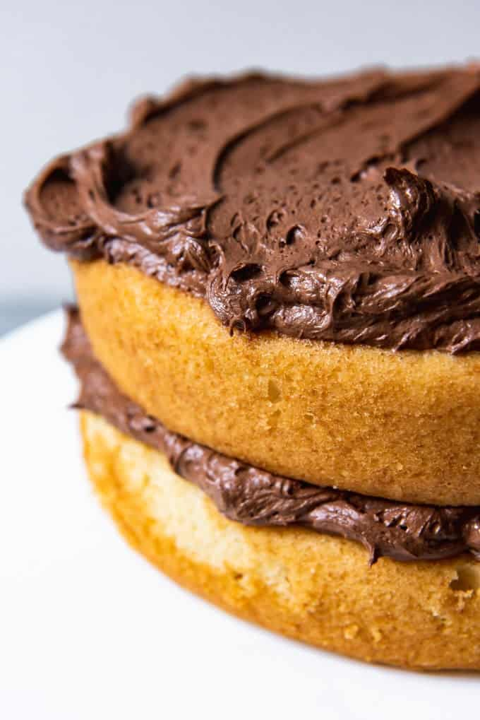 An image of layers of yellow cake being frosted with chocolate buttercream frosting.